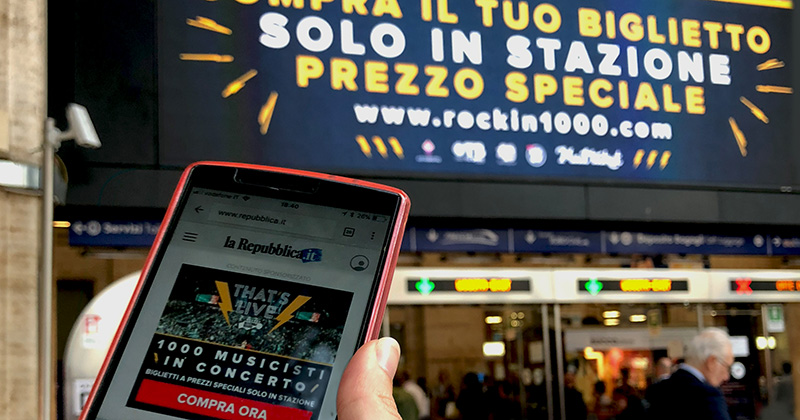 Smartphone and billboard with ads for ROCKIN'1000 THAT'S LIVE 2018
